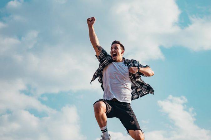 man jumping from a rock - Feliz - Horóscopo